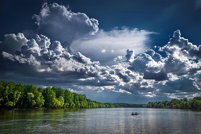 Billowing clouds over body of water